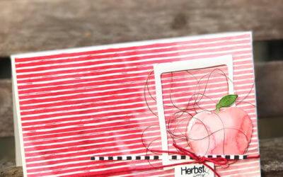 Gestreifter Apfel auf weißem Rahmenfaden